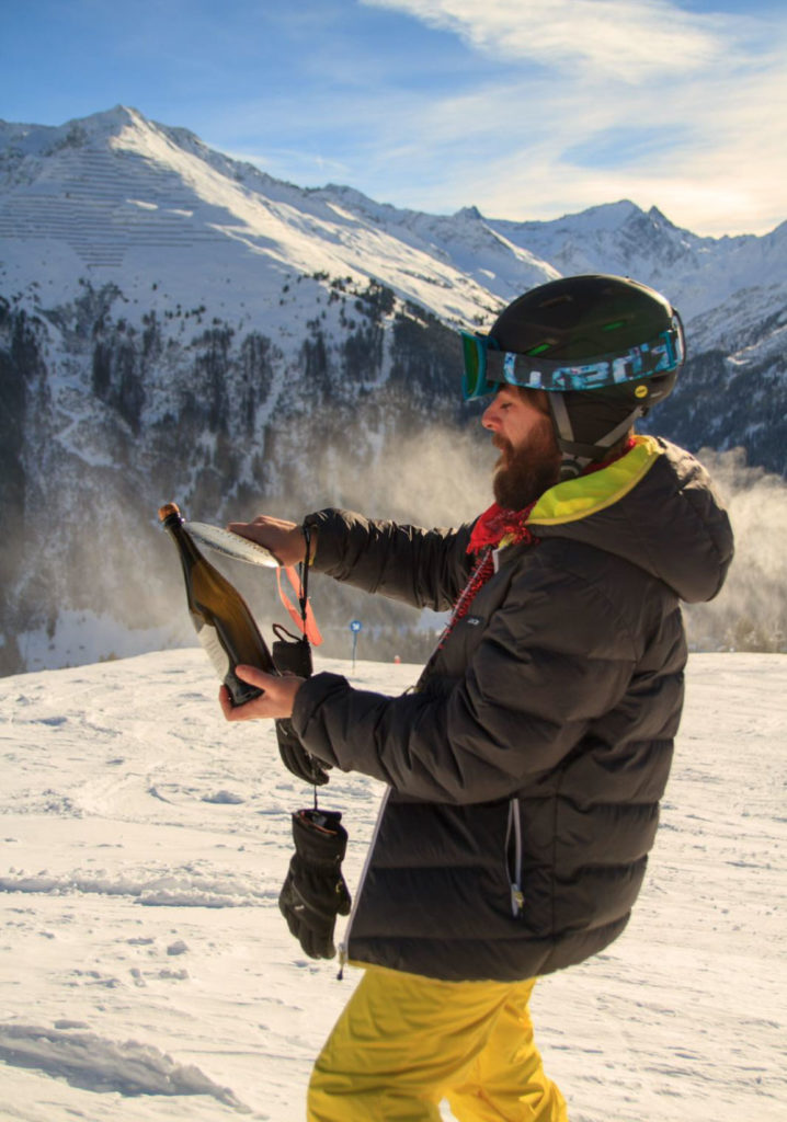 Chalet host opening champagne on the mountain. Chalet host vacancy - ski season jobs.