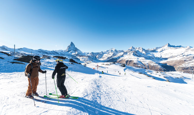 Skiers at the top of the mountain looking over luxury ski chalets in Zermatt