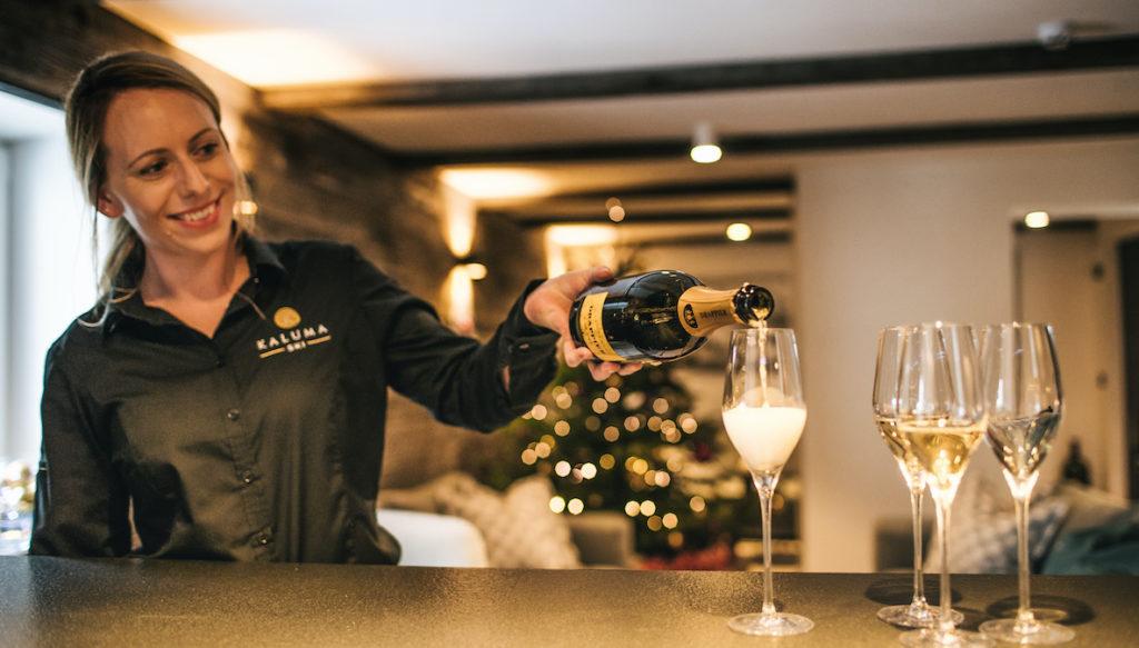 Chalet 47 staff pouring glasses of champagne Christmas skiing time