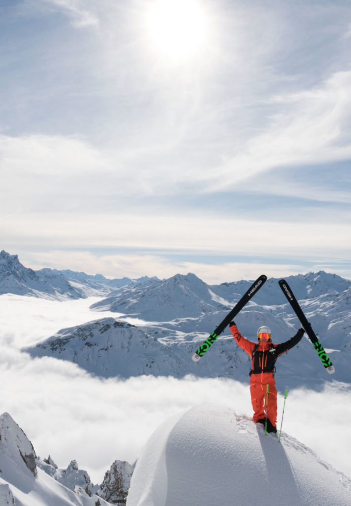 Skier on top of mountain waving skis,