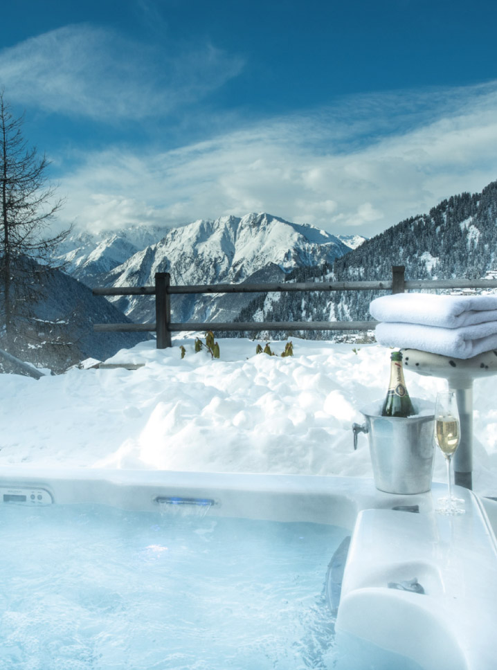 Outdoor hot tub with mountain view and champagne at Chalet Rock, Verbier