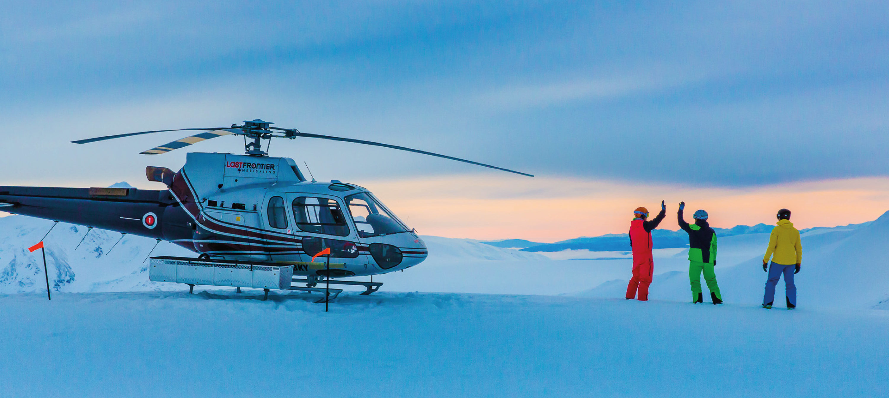 Heliskiing in British Columbia - Helicopter and skiers on mountain