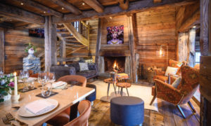 Open plan living and dining area with open fireplace at Chalet Montana, Courchevel 1850