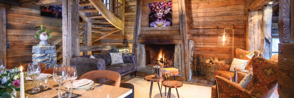 Living and dining area with open fireplace at luxury ski chalet in Courchevel 1850