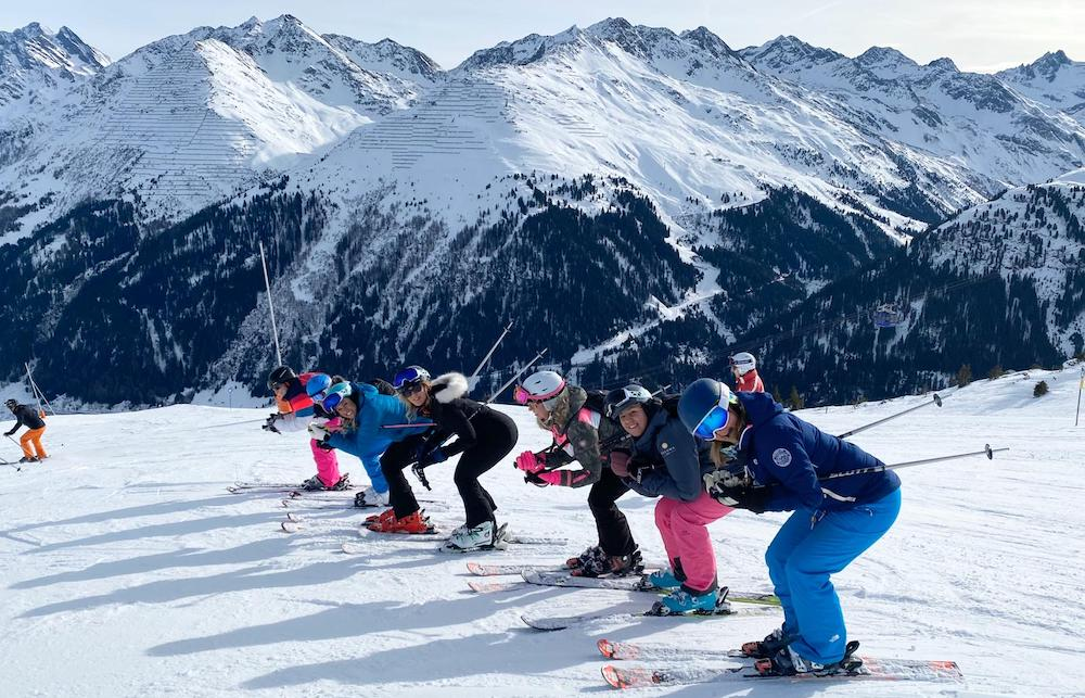 Women lined up on the Women Who Ski trip ready to ski off