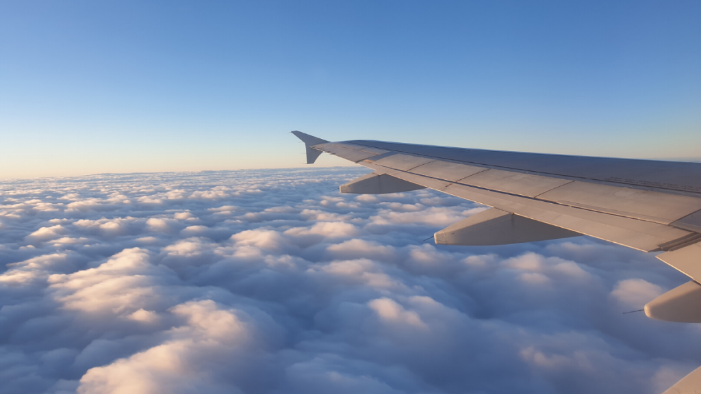 View over plane wing above the clouds - a dream after Covid-19