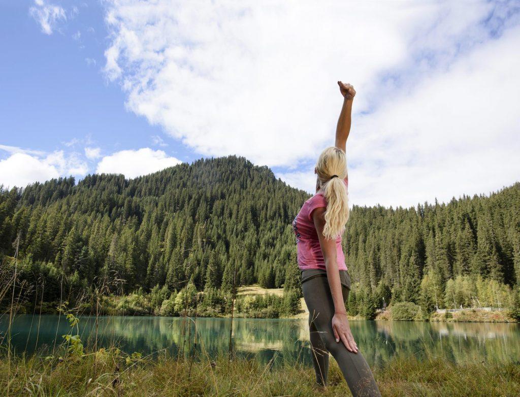 Yoga pose by a lake near St Anton